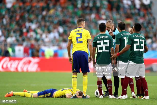 Ola Toivonen of Sweden lies on the pitch injured while Mexico player discuss with Referee Nestor Pitana during the 2018 FIFA World Cup Russia group F...