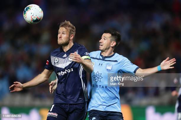 Ola Toivonen of the Victory is challenged by Ryan Mcgowan of Sydney FC during the round 1 ALeague match between Sydney FC and Melbourne Victory at...