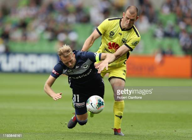 Ola Toivonen of the Victory is challenged Luke De Vere of the Wellington Phoenix during the round 10 A-League match between the Melbourne Victory and...