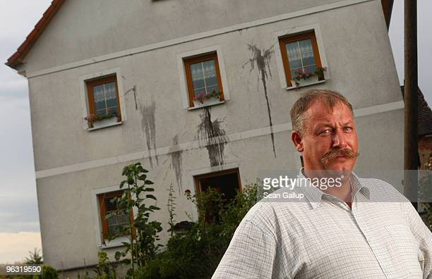 Olaf Bonk heating system installer and local politician for the businessoriented FDP political party stands in front of his vandalized house on July...