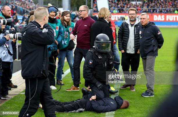 Olaf Janssen head coach St Pauli reacts while a supporter of Kiel is arrested by the police the Second Bundesliga match between Holstein Kiel and FC...