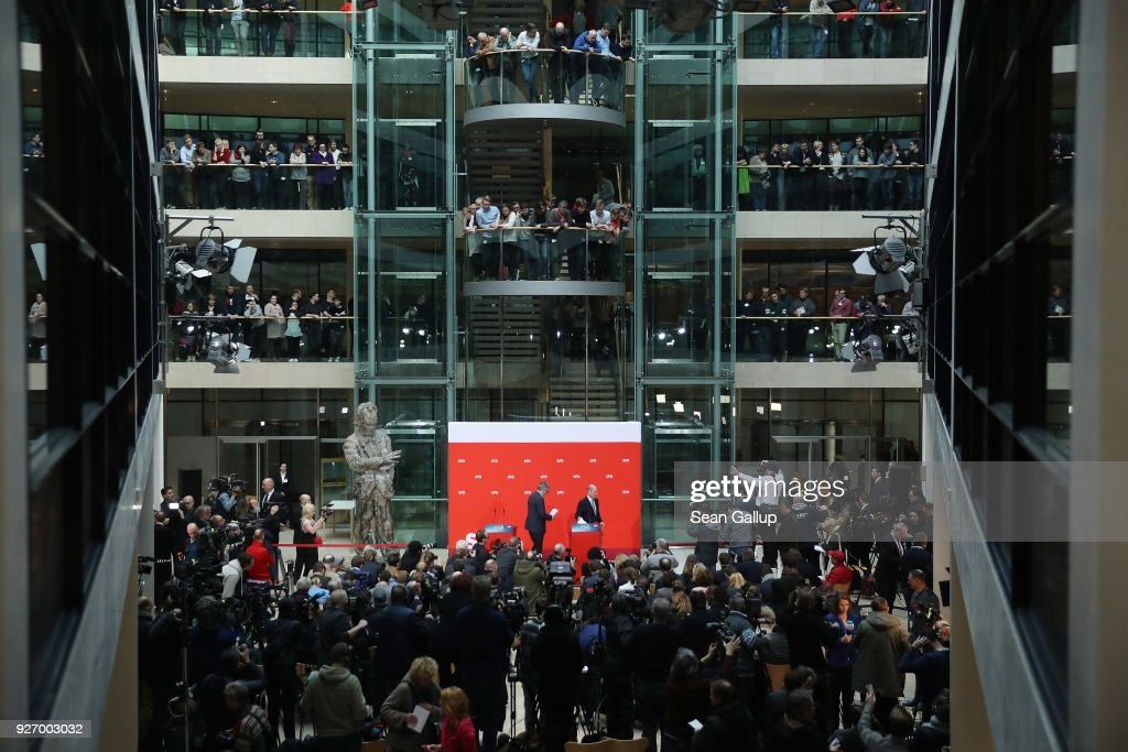 Olaf Scholz (R), Acting Chairman of the German Social Democrats (SPD), and SPD Treasurer Dietmar Nietan depart after speaking to journalists following the SPD member vote over the party's coalition contract with the German Christian Democrats (CDU/CSU) as SPD members look down from aboveat SPD headquarters on March 4, 2018 in Berlin, Germany. SPD members voted with 66% for the coalition, ensuring the creation of the next German coalition government later this month.