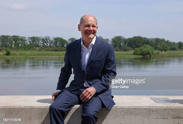 Olaf Scholz, German finance minister and chancellor candidate of the German Social Democrats , sits on the bank of the Elbe River while attending a...