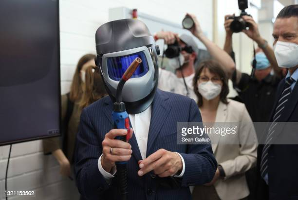 Olaf Scholz, German finance minister and chancellor candidate of the German Social Democrats , tries on a welding helmet while visiting the SLV Halle...