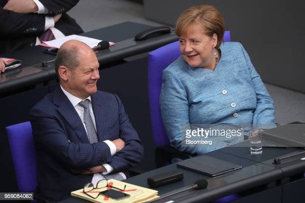 Olaf Scholz Germany's finance minister left reacts as he sits beside Angela Merkel Germany's chancellor during a budget policy plan speech in the...
