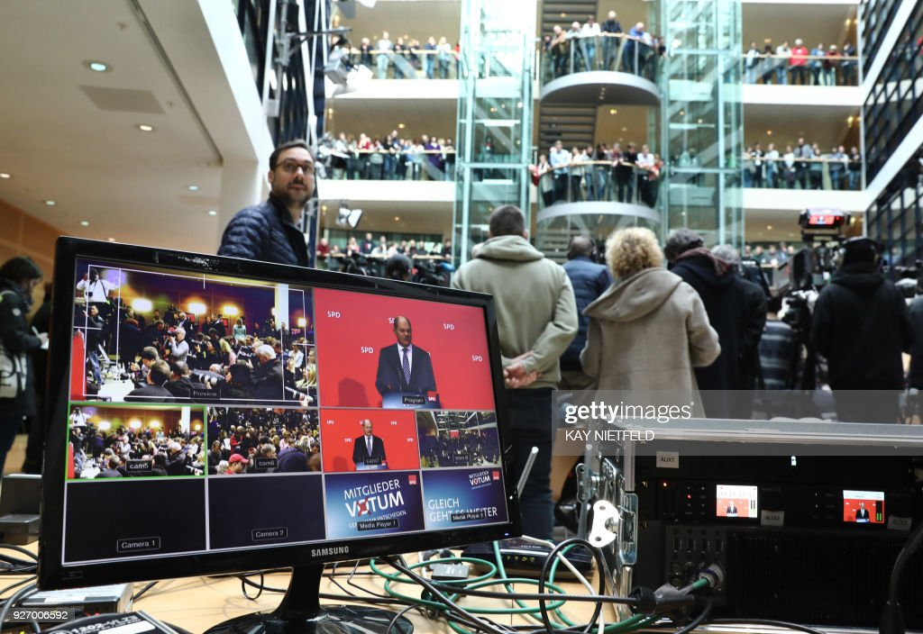 Olaf Scholz, interim leader of Germany's Social Democrats (SPD) party, is displayed on a screen as he speaks after the the result of the SPD party members' referendum was announced on whether or not to join a new coalition government with German Chancellor Angela Merkel's conservatives, during a press conference on March 4, 2018 at the SPD headquarters in Berlin. The members of Germany's second biggest party have in their high-stakes referendum approved a plan to join Chancellor Angela Merkel's coalition. The make or break vote was the last hurdle in the way of Merkel's fourth term in office and essentially ends a political stalemate that has plagued the country since September's inconclusive elections. / AFP PHOTO / DPA / Kay NIETFELD / Germany OUT