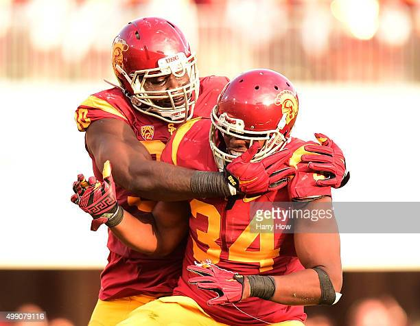 Olajuwon Tucker and Claude Pelon of the USC Trojans celebrate a third down stop of the UCLA Bruins during a 4021 Trojan win at Los Angeles Memorial...