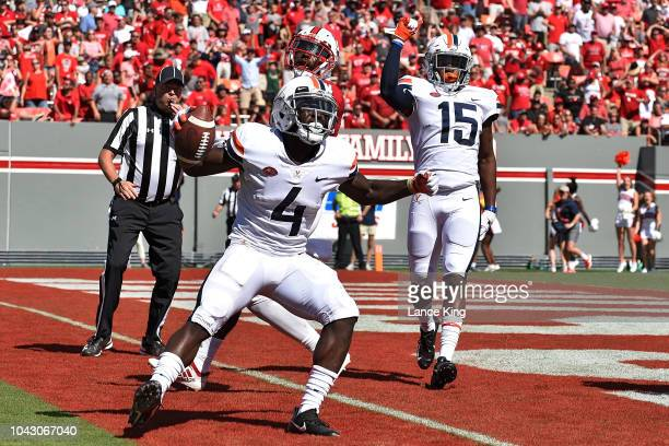 Olamide Zaccheaus of the Virginia Cavaliers reacts following a nineyard touchdown reception against the North Carolina State Wolfpack at CarterFinley...