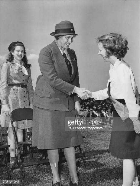 Olave BadenPowell Chief Guide of Britain and widow of Robert BadenPowell shakes hands with girl scout Flora Ann Campbell during a meeting of Girl...