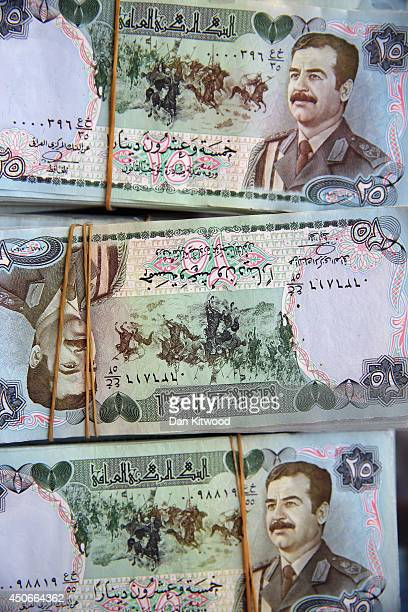 Old 25 Dinar notes with a portrait of Saddam Hussein and medieval horsemen are sold in the Qaysari Market on June 15 2014 in Erbil Iraq In Iraq's...