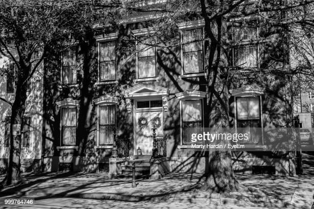 old abandoned building by trees in city - marty hardin stock photos and pictures