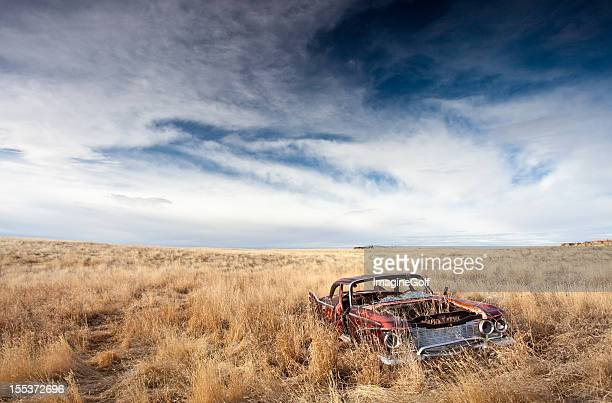 old abandoned car on the plains - abandoned car stock photos and pictures