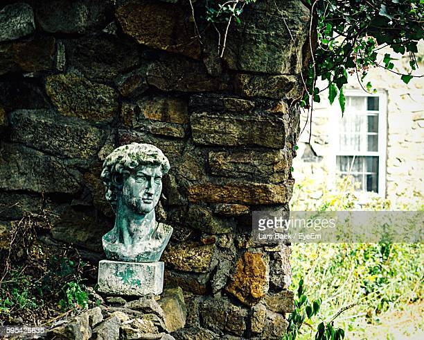Old Abandoned Male Bust Against Stone Wall