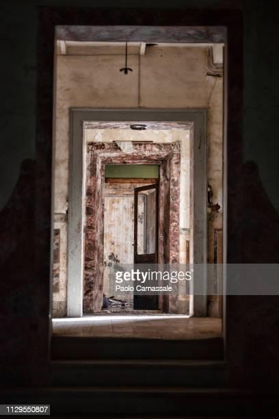 old abandoned residential corridor with open door at the end - nederzettingen stockfoto's en -beelden