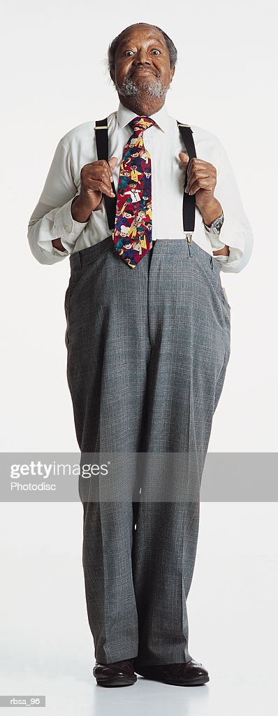 old african american adult male with gray hair and facial hair wearing  a white shirt and bright tie with gray slacks and suspenders stands alertly while holding his suspenders away from his chest and looking at the camera with a humorous smile and t : Foto de stock