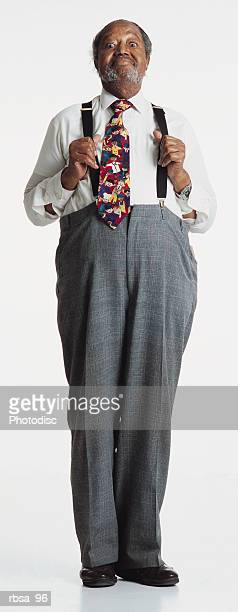 old african american adult male with gray hair and facial hair wearing  a white shirt and bright tie with gray slacks and suspenders stands alertly while holding his suspenders away from his chest and looking at the camera with a humorous smile and t