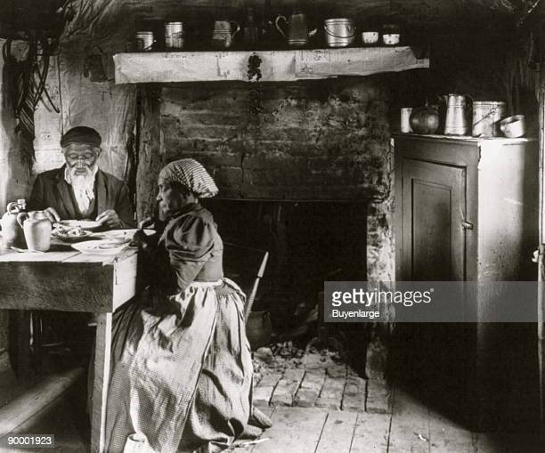 Old African American couple eating at the table by fireplace rural Virginia