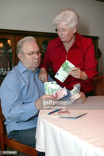 Old age pensioner couple with a household book and Euro notes Symbolic picture pension cutting of the pensions poverty in the old age