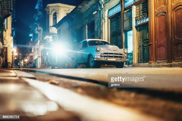 old american car in old havanna street at night - old havana stock pictures, royalty-free photos & images