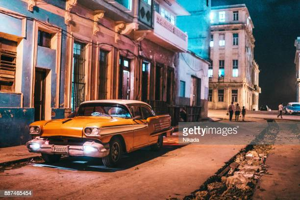 old american car parking on street at dusk, havana, cuba - cuba 1950s stock photos and pictures