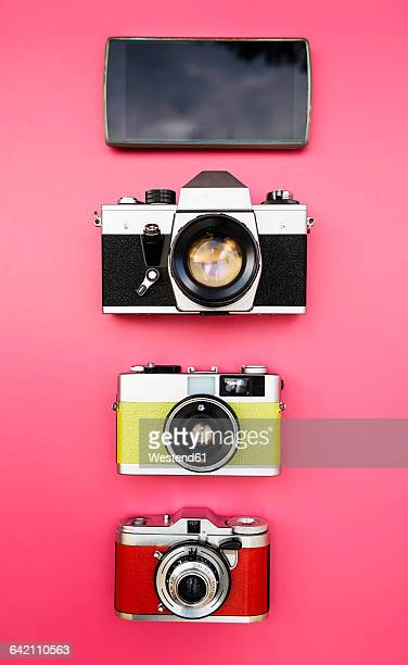 Old analog cameras and smartphone on a pink background