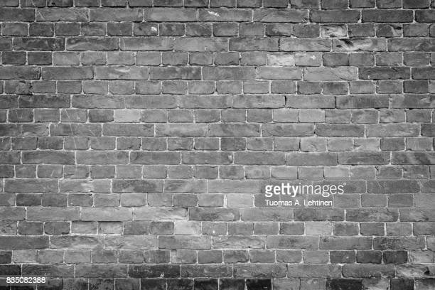 Old and aged brick wall texture background with vignetting in black and white.