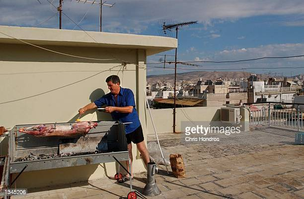 Old and new In downtown Piraeus the port of Athens resident George Malegos cooks a lamb on a spit on the roof of his apartment building August 14...