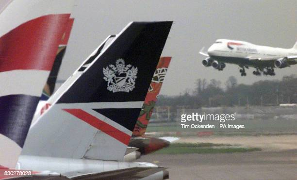 Old and new tail fin designs on British Airways aircraft at Heathrow Airport The company reported a 40% slump in profits as cutthroat competition for...