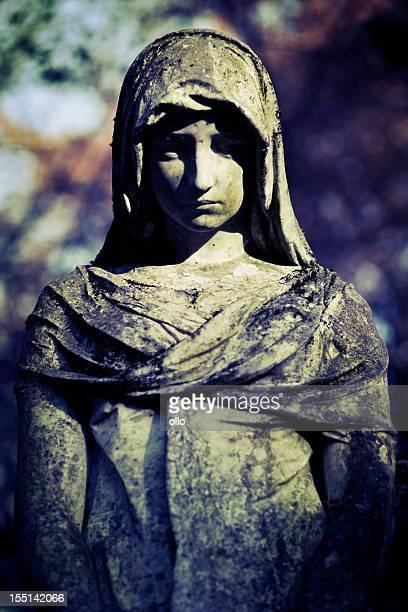 Alte, verwitterte statue auf einem verlassenen grave
