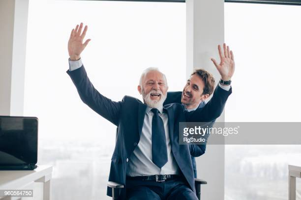 old and young business men having fun at office - solo adulti foto e immagini stock