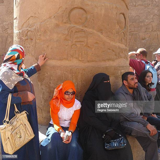 CONTENT] Old and young Egyptians getting in touch with their 5000 year old history by touching the hieroglyphs on the colums in Luxor with their...