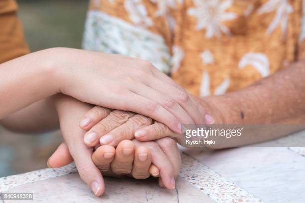 old and young holding hands, care for the elderly concept - hospice stock pictures, royalty-free photos & images