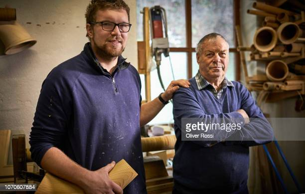 old and young instrument maker in workshop with alpenhorn instrument parts - successor stock pictures, royalty-free photos & images