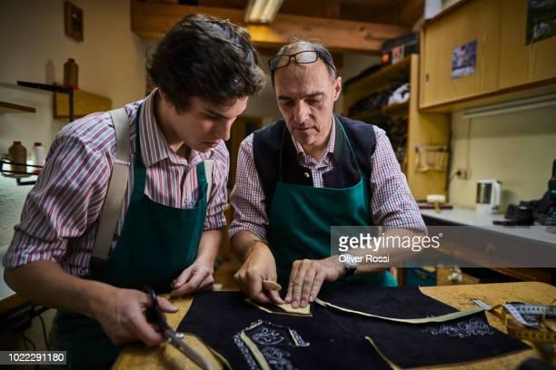 old and young tailor in workshop making bavarian lederhosen - tradition stock-fotos und bilder