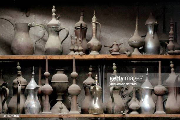 old arabian style coffee pots in a market stall - manama stock pictures, royalty-free photos & images