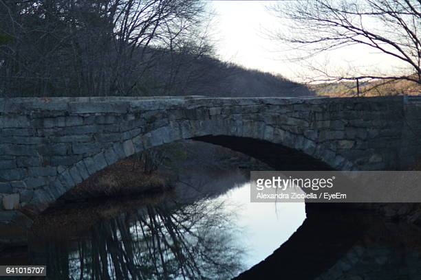 Old Arch Bridge Over Calm River Against Sky
