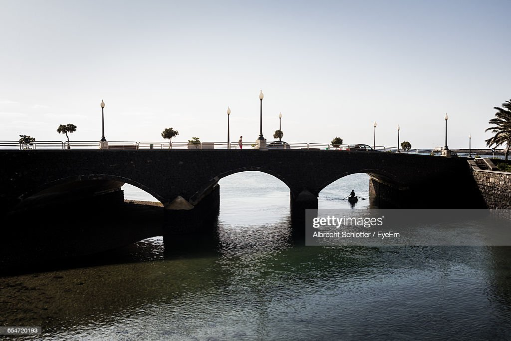 Old Arch Bridge Over Sea At Lanzarote Against Sky : Stock Photo