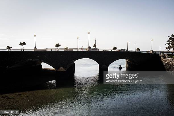 old arch bridge over sea at lanzarote against sky - albrecht schlotter stock photos and pictures