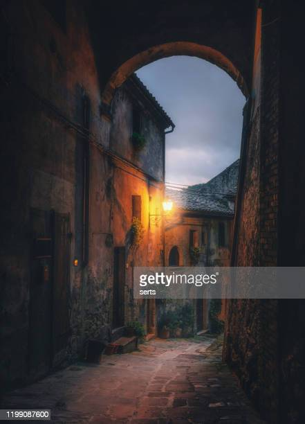 old arched cobblestone street at night in medieval town sorano, tuscany, italy - old town stock pictures, royalty-free photos & images