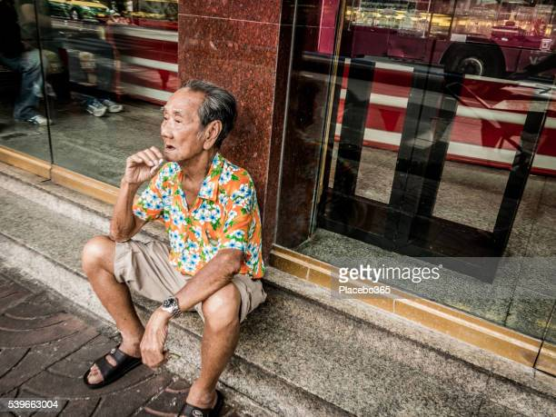 old asian man sitting smoking cigarette on street - emphysema stock photos and pictures