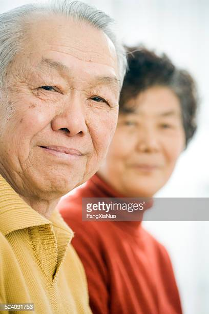Old Asian man smiling besides his wife