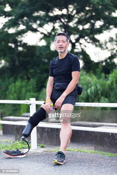Oude atleet met een kunstmatige been nemen van een pauze na een vermoeiend uitvoeren