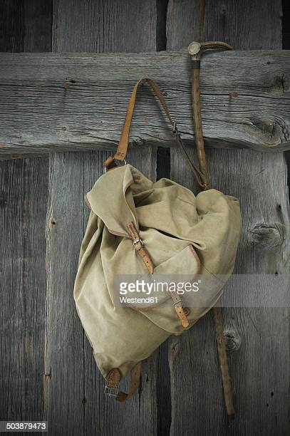 Old backpack and walking stick hanging on wooden wall