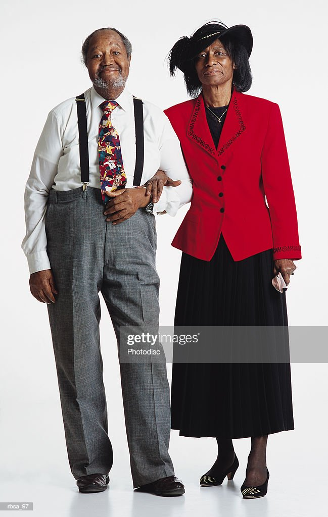 old balding african american smiling adult male with facial hair wearing a white shirt and bright tie and gray slacks with suspenders standing arm in arm with an old african american adult female wearing a featherd felt hat and a red blazer over a bl : Foto de stock