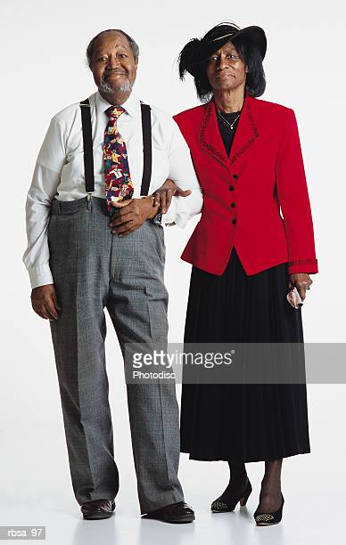 old balding african american smiling adult male with facial hair wearing a white shirt and bright tie and gray slacks with suspenders standing arm in arm with an old african american adult female wearing a featherd felt hat and a red blazer over a bl - 一張羅 ストックフォトと画像