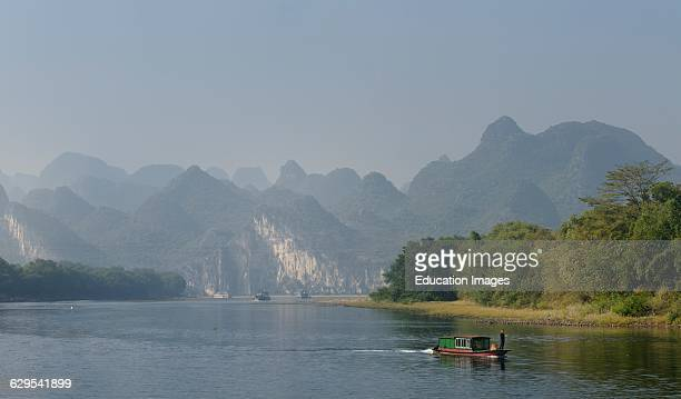 Old barge and cruise boats on the Li River Guangxi China with karst dome mountains