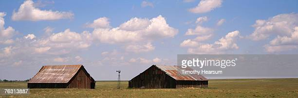 old barns with rusty metal roofs in open field - timothy hearsum stock pictures, royalty-free photos & images
