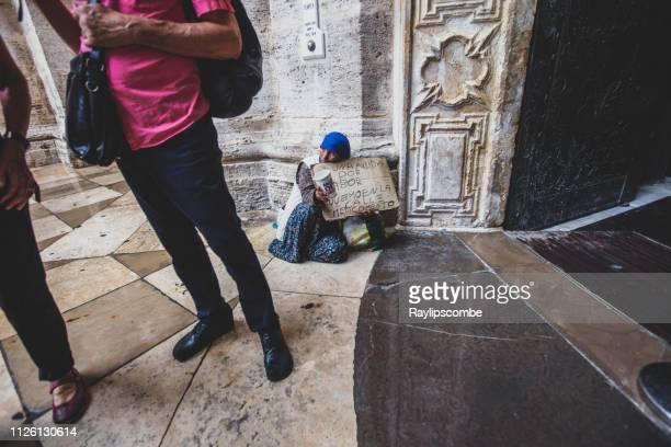oude bedelaar vrouw met een mcdonalds kopje buiten een kerk in de stad van valencia, spanje - europese cultuur stockfoto's en -beelden