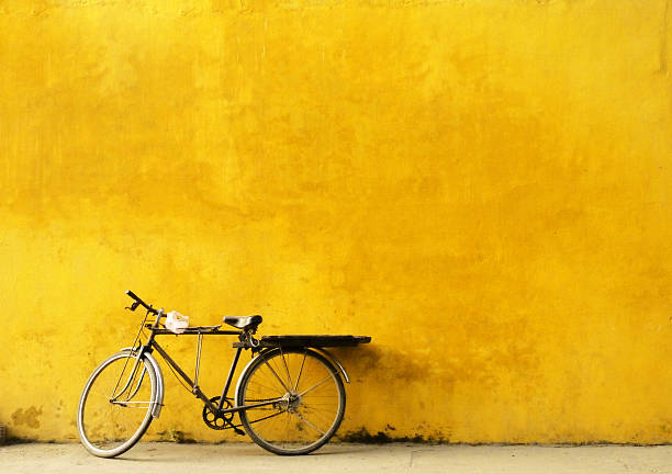 Old Bicycle Parked Against Worn Yellow Wall Wall Art