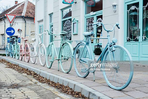 Old bicycles painted in pastel colors and connected used as fence outside cafe